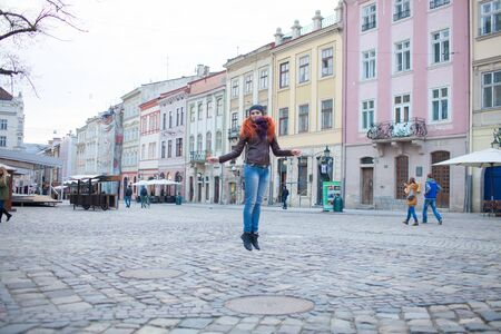 Backgrounds and textures. Red-haired girl on the town square having fun on the background of old buildings