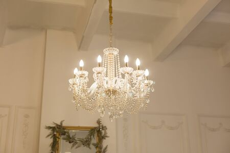 Chandelier in a white room in a classic design Фото со стока