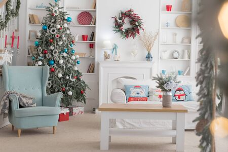 The interior of the Christmas room, a white sofa with pillows at the coffee table and a blue chair