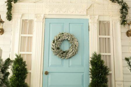 Christmas wreath on the blue door with garlands