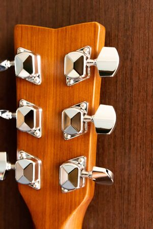 Acoustic guitar neck on a wooden background. Pin mechanism. Backgrounds and textures