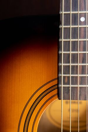 Sound hole of an acoustic guitar, neck, strings, frets, the nut.