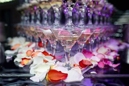 wedding reception decoration: martini glasses on served table in a restaurant with flowers