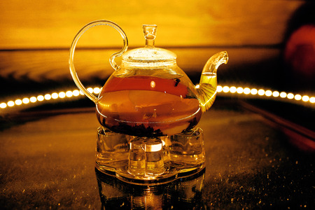 Glass teapot with hot tea on the fruit in the cafe