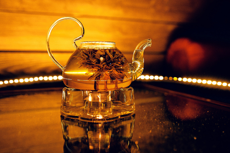 Glass teapot with hot tea and a lotus flower in a cafe