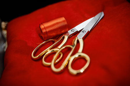 Amazing photo  of silver scissors with golden handle near silk ribbon on the silk cloth