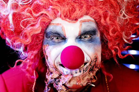 evil clown for Halloween in scary makeup with lenses in the form of a spider web Foto de archivo