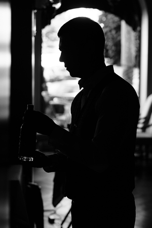 Atmospheric photo of man with bottle of wine at the dark tunnel