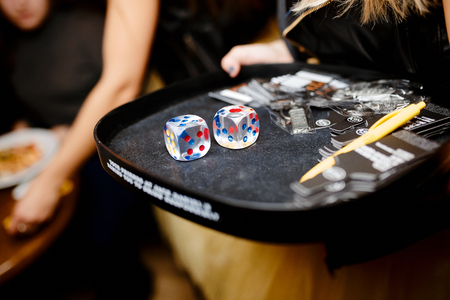 Two transparent playing dice on a black tray in a girl with a pen
