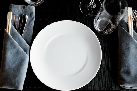 Cutlery folded in a gray napkin and a white plate are on the table in the restaurant