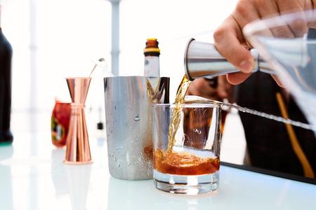 Camarero vierte whisky en un vaso de pie sobre una mesa en un restaurante
