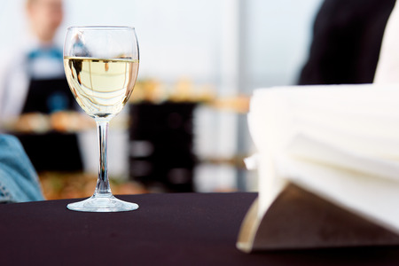 a glass of white wine on a table with a black tablecloth and a waiter in the background in a restaurant