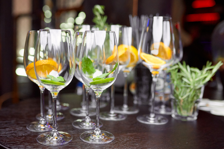 wine glasses filled with lemon, lime and mint on a brown table in the restaurant