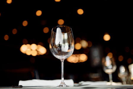 empty wine glass on the table with lights on the background