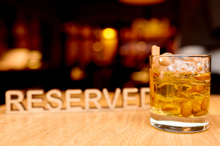 metal plate reserved with glass of whiskey on the table in the restaurant Stockfoto