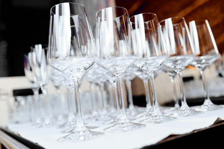 empty wine glasses on a white tablecloth on a table in a restaurant