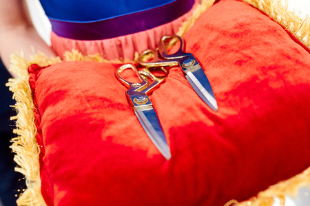 big scissors on the red pillow in womans hands