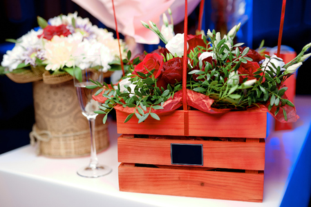 beautiful flower bouquets in boxes on a table next to champagne glass Stockfoto