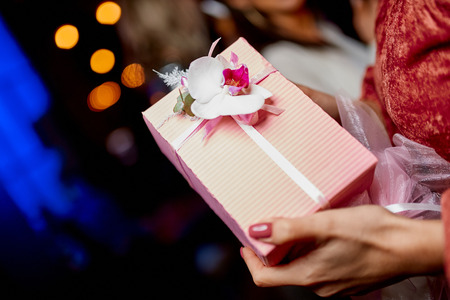 gift wrapped in pink packaging  in the hands of a girl