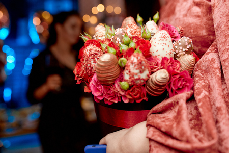 a bouquet of strawberries in chocolate and roses in the hands of a girl, with a girl in the background Stockfoto