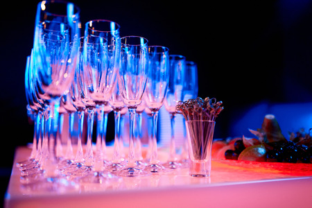 empty champagne glasses in neon light, next to toothpicks on a table in a restaurant Stockfoto