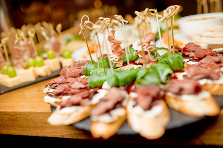 various types of canapes from cheese, grape,meat, tomatoes, olives on the table in the restaurant