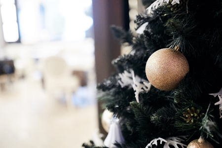 Christmas tree decorations on a tree with a table and chairs in the background