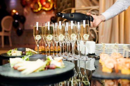 glasses of champagne, which waiter pours, with appetizers on the table in the restaurant Stockfoto