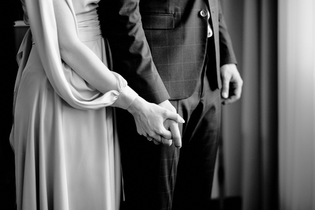 female hand holds male hand in black and white at the room