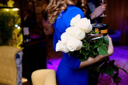 girl in a blue dress holding white roses at a wedding in a restaurant