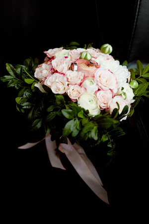 bridal bouquet of pink and white peonies, with the addition of greenery and white gold rings lying on it