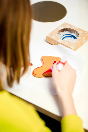 the woman decorates gingerbread in the form of mittens on the table Stockfoto