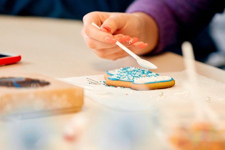 the woman decorates gingerbread in the form of mittens on a napkin on the table