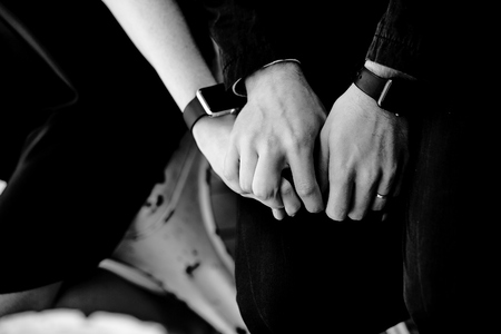 male hands hold female hand in black and white at the room Stockfoto
