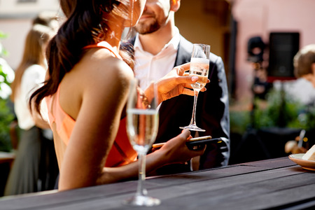 a man in a suit smiles at a girl in a dress that holds a glass of champagne outdoors at a wedding Stockfoto