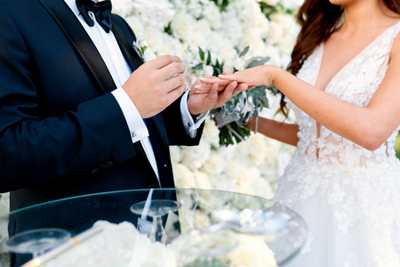 a man in a black suit puts a ring on his brides finger in beautiful dress Stockfoto
