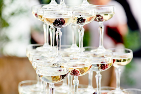 glasses of champagne with a frozen berries outside at a wedding