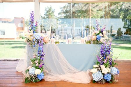 table de mariage pour les jeunes mariés, très joliment décorée avec des fleurs et des bougies et une nappe Banque d'images