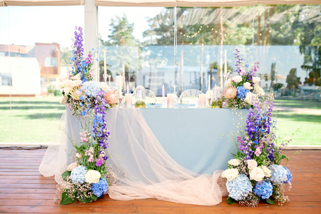 wedding table for newlyweds, very beautifully decorated with flowers and candles and a tablecloth Reklamní fotografie