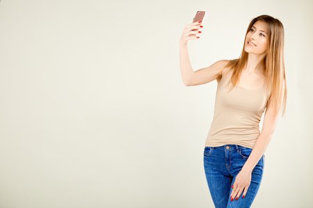beautiful girl in a beige T-shirt and blue jeans stands against a gray wall making a selfie with a smile