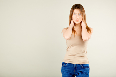 a girl in a beige T-shirt and blue jeans is standing against the gray wall and playfully looking at the camera with her mouth slightly open flirting with her eyes with her hands on the neck