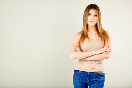 girl in a beige t-shirt and blue jeans is standing against the gray wall is looking at the camera with her arms crossed slightly smiling