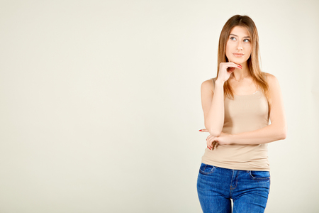 a girl in a beige T-shirt and blue jeans is standing against a gray wall and looking to the side and holding her right hand at the chin thinking about something good