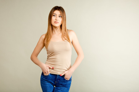 girl in a beige t-shirt and blue jeans is standing against the gray wall and looking to the side and holding her hands in her pockets Stockfoto