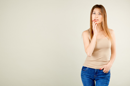 a girl in a beige T-shirt and blue jeans is standing against the gray wall and playfully looking at the camera with her mouth slightly open flirting with her eyes Stockfoto