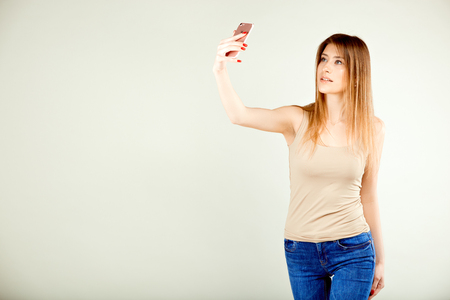 girl in a beige T-shirt and blue jeans stands against a gray wall making a selfie with a surprised facial expression