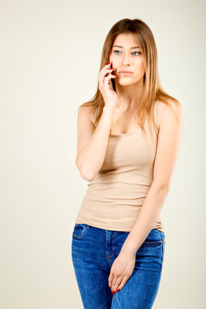a girl in a beige T-shirt and blue jeans stands against a gray wall talking on a mobile phone, clearly upset by the sad news