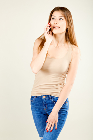 girl in a beige T-shirt and blue jeans standing on a gray wall background talking on a mobile phone and looking to the side smiling suspiciously Stockfoto