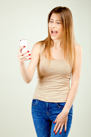 a girl in a beige T-shirt and blue jeans is standing against the gray wall, looking at the phone screen and screaming in surprise