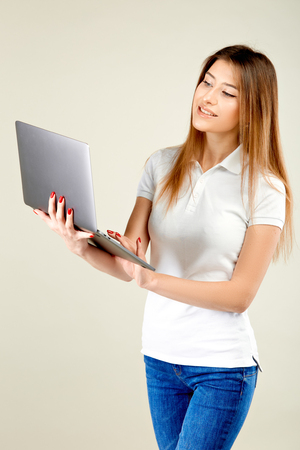 girl in a white polo t-shirt and blue jeans stands against a gray wall holding a laptop in her hand and looks at his screen in smile Stockfoto